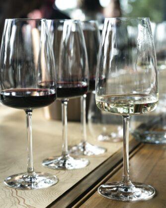 редица винени чаши в част от които има червено вино