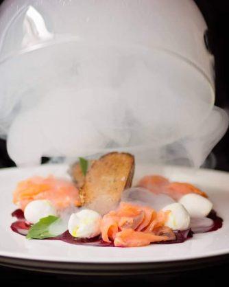 месно ястие под вдигнат похлупак с бял дим