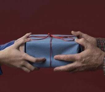четири ръце държат синя кутия с панделка