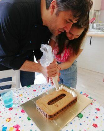 мъж и дете гарнират торта със сметанов крем
