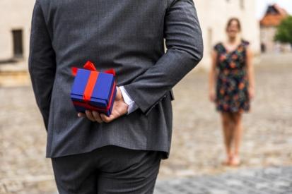 мъж в костюм държи син подарък зад гърба си