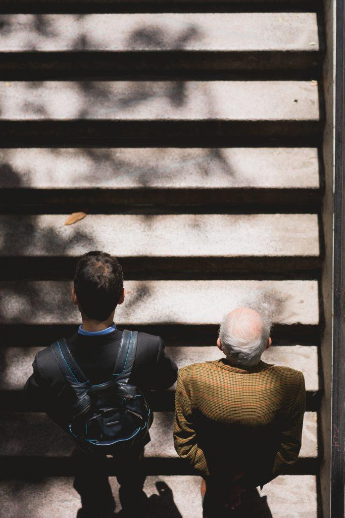 възрастен и млад мъж в гръб изкачват стълби