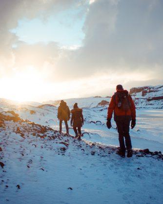 трима туристи в снежна панина огряни от слънцето