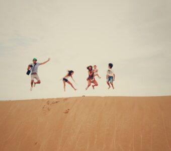 младежи скачат на пясъчна дюна