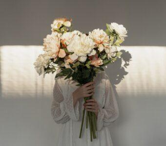 жена държи букет бели цветя пред лицето си