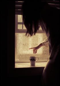 Жена, която гледа през прозореца