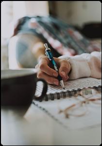 Ръка която пише със син химикал