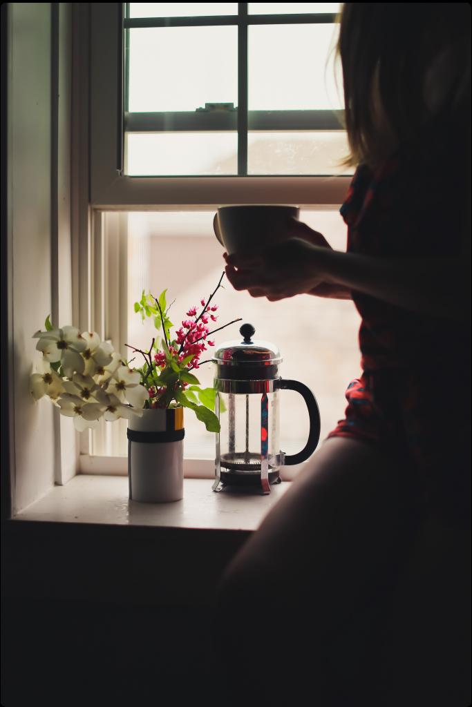 Жена седнала до прозореца с чаша чай в ръка