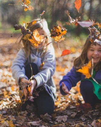 деца играят в есенни листа